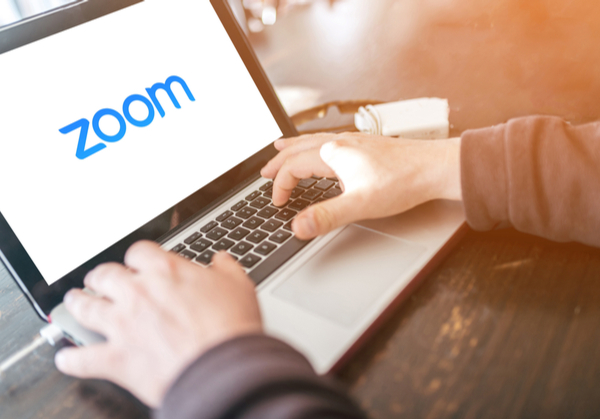 A person using a laptop using Zoom logo