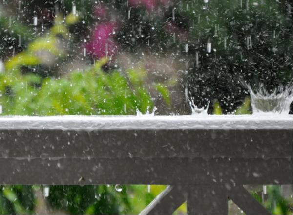 Rain drops crashing on balcony rail