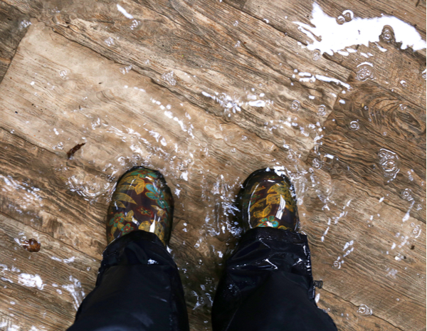 Waterproof rain boots are standing in a flooded house
