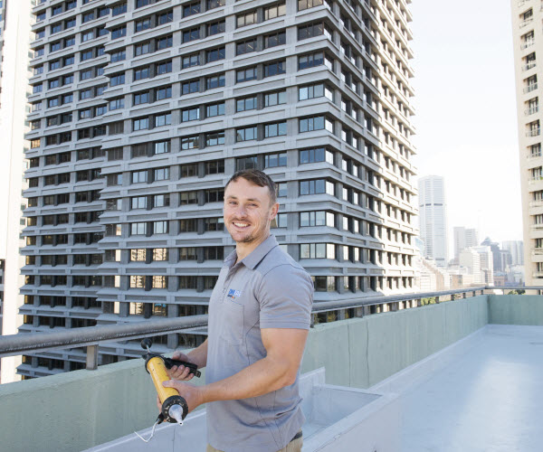 Man working on rooftop with buildings behind him