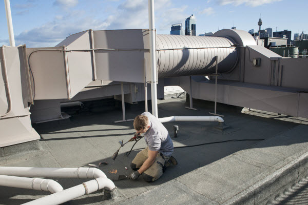 Man fixing floor leaks on rooftop