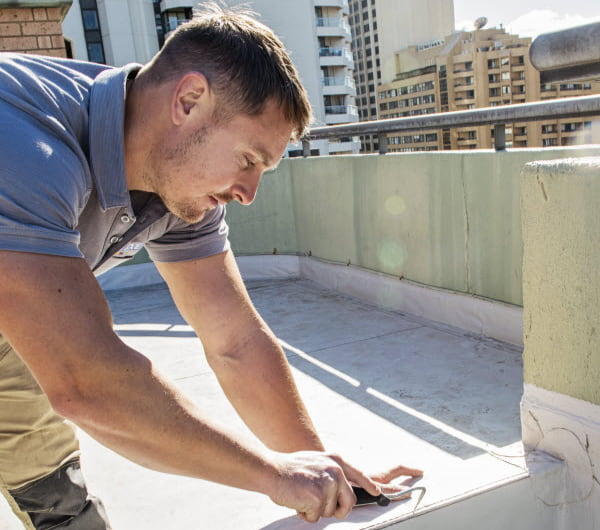 Man fixing a damaged concrete on the roof