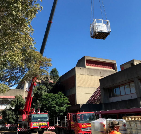 Truck crane lifting an equipment to the rooftop