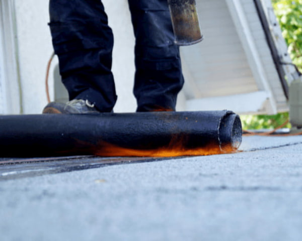 Flat roof installation with propane blowtorch