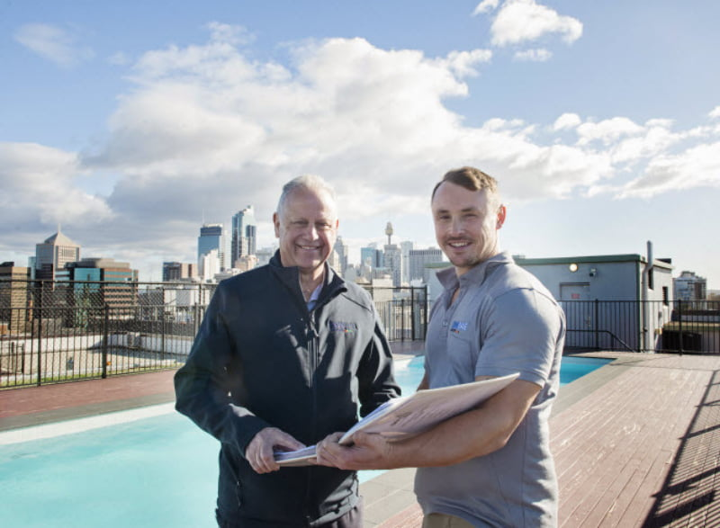 Two men standing in front of a pool on a roof and smiling at the camera while holding a book