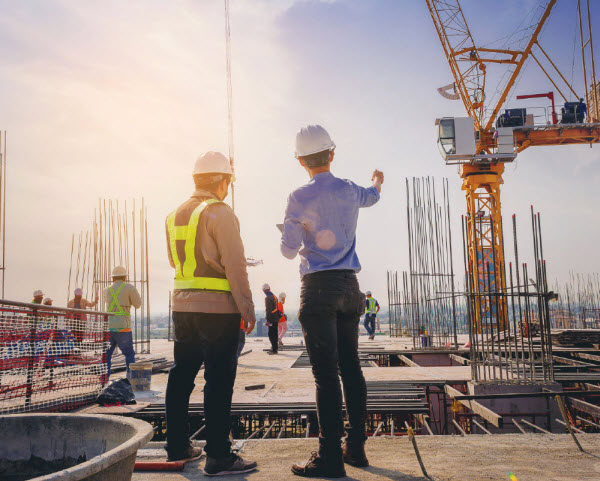 Two engineers wearing safety gears discussing at the top construction site