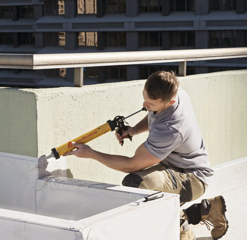 Man sealing a cracked wall on rooftop