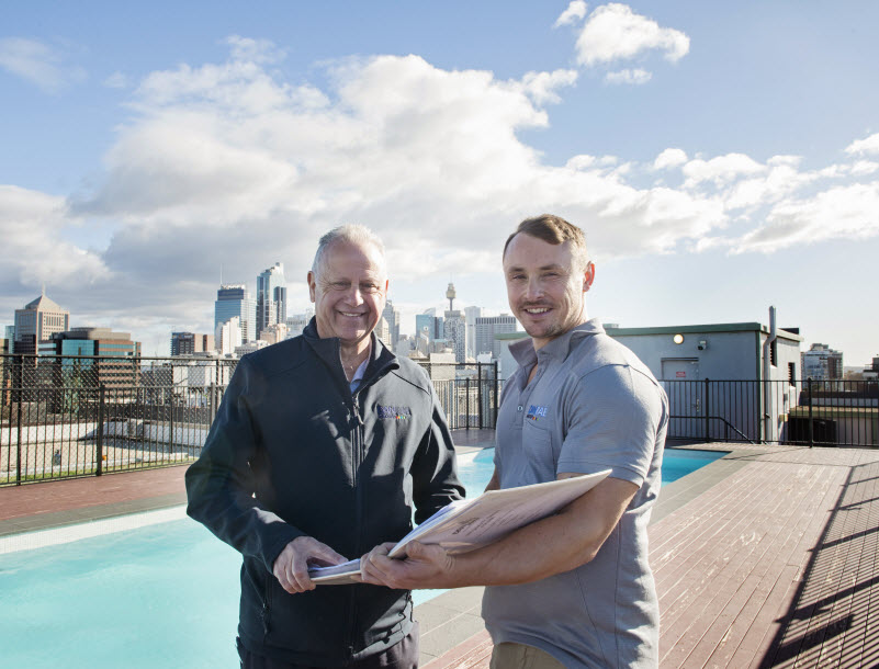 Two men checking a design while on the roof with a pool