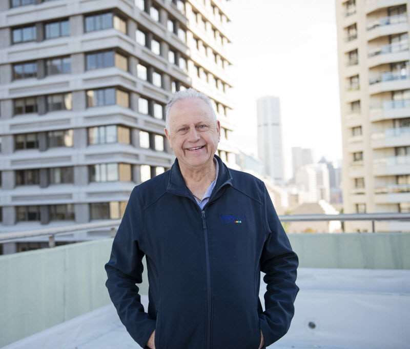 Man standing on a concrete roof smiling at the camera