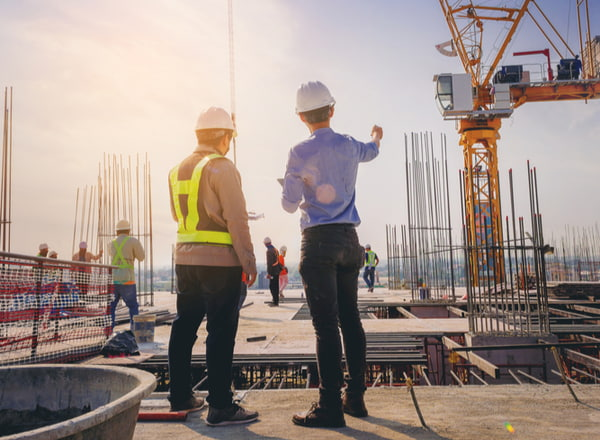 Structural engineer and foreman worker with touch pad discuss