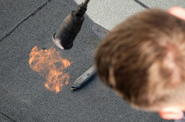Man using torch to melt the bitumen