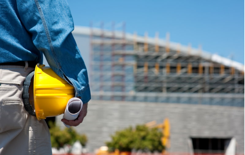 Foreman at a construction site with blue prints and a hard hat