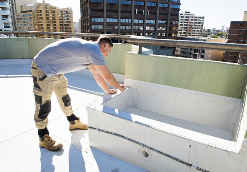 Man fixing the wall on rooftop