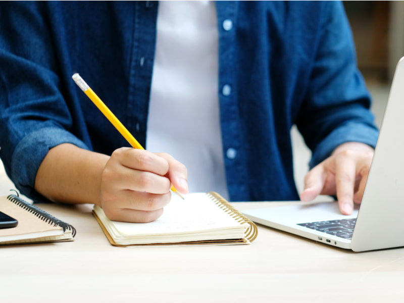 Student writing on notebook while study at home