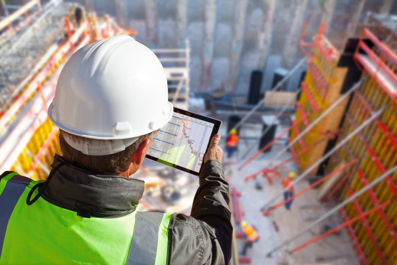 Engineer wearing hardhat on construction site checking schedule on tablet